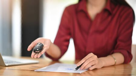 Close-up Young woman together with the car purchase agreement and keys. Banco de Imagens