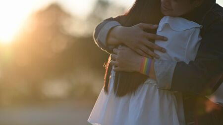 Cropped shot of young LGBT Lesbian couple embracing together at the beautiful park with the blurred sunset light as background. LGBT Happiness couple concept.