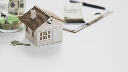 Close-up image of House model, saving money, key, agreement on clipboard and money putting together on white table. Concept of saving plan for purchase a property.