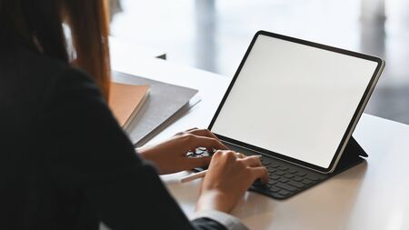 Behind shot of young businesswoman typing on tablet keyboard with white blank screen while sitting at the modern working desk.