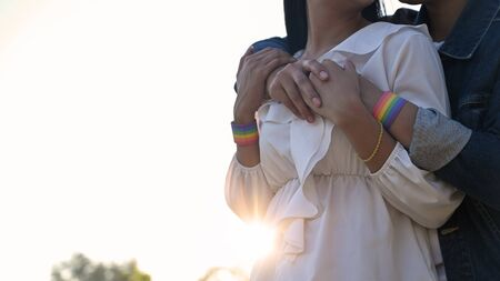 Cropped shot of young LGBT Lesbian embracing her lover from the back at the beautiful park with the sunset light as background. LGBT Happiness couple concept.