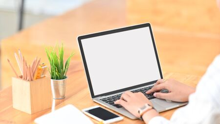 Cropped shot of young creative woman surfing the internet by using white blank screen laptop while sitting at the modern wooden desk.
