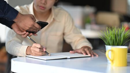 Cropped shot of young architect writing/drawing roughly the house architectural concept by copying from the customer smartphone.