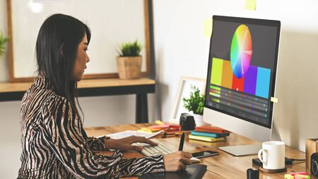 Creative designer sitting at wooden working desk using digital tablet for selecting color from color managementcolor palette program. Graphic design concept
