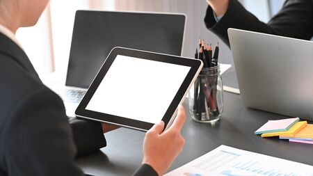 Behind shot of young businessman holding a white blank screen computer tablet while discussing about new business project at the modern meeting room.