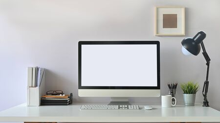 Photo of white blank screen computer  and office equipment is on the table. Modern working desk concept. Banco de Imagens