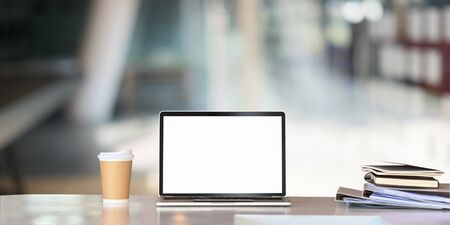 Mockup laptop computer, paper coffee cup, document file on business table with empty screen.