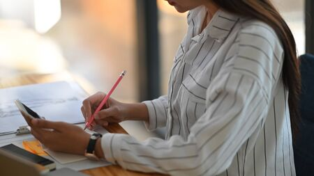 Cropped shot of young beautiful woman in striped shirt holding smartphone in hand and writing/taking note white sitting at the modern wooden desk with modern office as background.