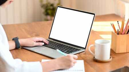 Cropped shot of young designer woman writing on notebook while she sitting and using white blank screen laptop at the modern wooden table. Women lifestyle concept.