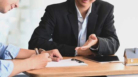 Cropped shot of Real estate agent offer house insurance or house ownership to smart man in blue shirt at the modern wooden table. Signing on agreement, Broker/Seller/Dealer concept.