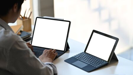 Smart man working as accountant typing on white blank screen computer tablet with keyboard case while sitting at the modern working desk with orderly office as background.