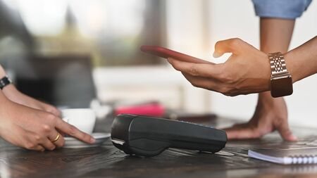 Cropped image of man using a smartphone for making a bill payment at credit card reader with the cafe cashier counter as background. NFC technology concept. Stock Photo