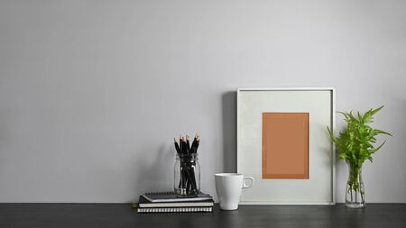 Photo of notes, diary, picture frame, potted plant, coffee cup and pencil holder putting together on modern working table with white wall as background. Orderly workplace concept.