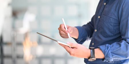 Photo of smart businessman holding a computer tablet and stylus pen while standing in the comfortable office with blurred office glass wall as background.