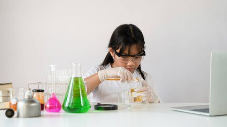 Photo of adorable schoolgirl doing a scientific experiment at the modern white table with chemistry glassware over the white laboratory wall as background. Education for kids concept.