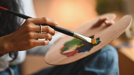 Cropped image of artist woman's hand drawing an oil color on canvas by paint brush at the modern art studio. Young artist/Painter concept.