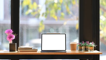 Photo of white blank screen computer tablet with keyboard case putting on wooden desk with potted plant, stack of books and takeaway coffee cup over cafe glass wall as background. Фото со стока