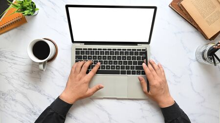 Top view image of businessman's hands typing on computer laptop keyboard with white blank screen that putting on marble texture table surrounded with coffee cup, pencil holder, potted plant and books.