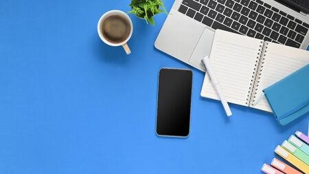 Photo of Blue working desk with office equipment putting on it. Flat lay Computer laptop, Coffee cup, Marker pens, Potted plant, Black blank smartphone and Notebook. Modern/Orderly workplace concept. Banco de Imagens