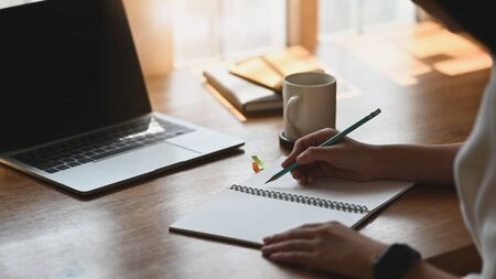Photo of beautiful woman working as writer taking notes while sitting in front a computer laptop that putting on wooden table with coffee cup and notebook. Compose/Poet/Writer concept.