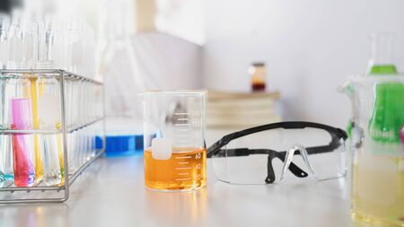 Photo of scientific experiment desk with chemistry glassware, stack of books, colored liquids and safety glasses putting on it. Concept of orderly workplace for the scientist.