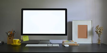 Photo of Workspace blank screen computer monitor putting on working desk and surrounded by picture frame, pencil holder, stack of books, wireless mouse, keyboard, coffee cup and wild grass in vase. Zdjęcie Seryjne