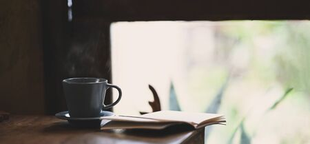Ceramic coffee cup with small dish putting on wooden table together with notebook over vintage living room as background. Orderly reading corner concept.