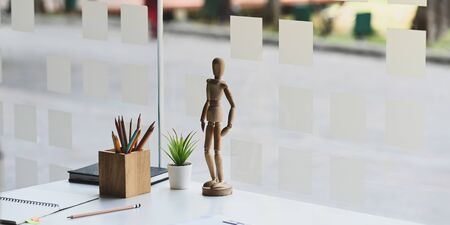 Wooden model putting on creative working desk that surrounded by wooden pencil holder, notebook, note, pencil and potted plant. Stationary and office equipment putting together.