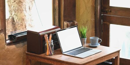 Computer laptop with white blank screen putting on wooden working desk and surrounded by coffee cup, potted plant, pencils in glass vase and transistor radio at sitting room reading corner. Stock Photo