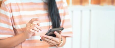 Cropped image of attractive woman hands holding/using a smartphone while standing over comfortable sitting room as background. Stock Photo