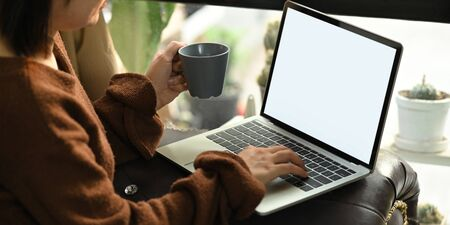 Cropped image of beautiful asian woman holding a coffee cup in hand while sitting in front her computer laptop with white blank screen that putting on her lap at the leather couch in living room.