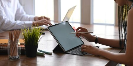 Cropped image of business people working with white blank screen computer tablet and laptop while sitting together at wooden working desk over comfortable working room windows as background.