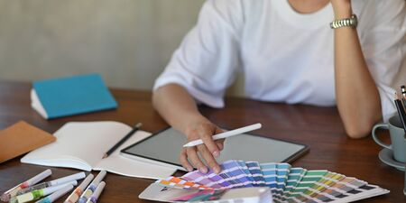 Photo of young graphic designer holding a stylus pen while selecting color from color guide and sitting in front of computer tablet with empty screen that putting on wooden working desk. Stock Photo