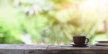 Coffee morning concept, coffee cup with small dish putting on old plank together with stack of notebook over forest outside as background.