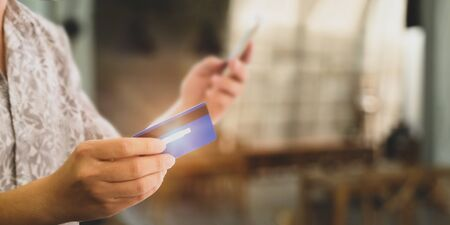 Cropped image of customer's hand holding a smartphone and credit card for doing a payment by using a credit card over blurred restaurant as background. Stock Photo