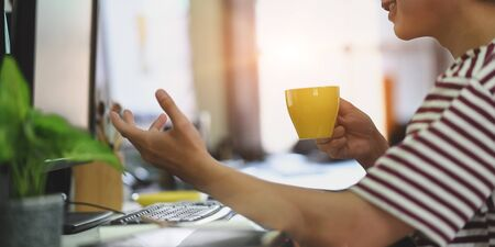 Cropped image of smart man in striped t-shirt drinking a hot coffee while sitting and working with computer at the white working desk in the morning vibe.