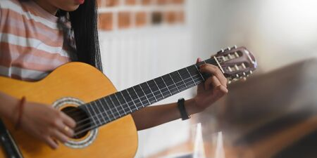 Cropped image of young asian woman practicing her skill on acoustic guitar while sitting over sitting room white wall as background. Woman with performing an acoustic guitar concept. Stock Photo