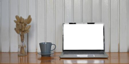 Photo of white blank screen computer laptop putting on wooden table and surrounded by wild grass in glass vase and ceramic coffee cup over modern living room wall as background. Фото со стока