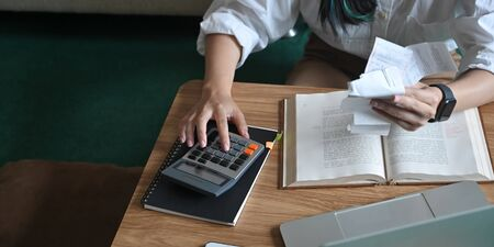 Closeup calculating and holding an Invoice while sitting at the wooden short legs table that surrounded by laptop and equipment over comfortable sitting room as background.