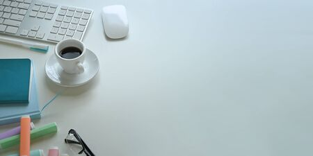 Top view image of coffee cup putting on white working desk that surrounded by wireless mouse, keyboard, marker pens, eye glasses, notebook, note and pen. Stock Photo