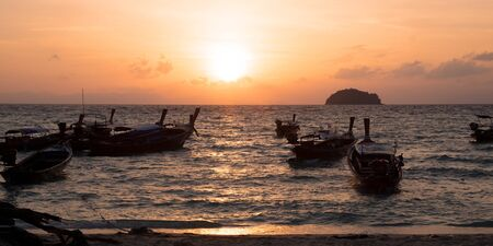 Seashore in the moment of sunset is surrounding by Thailand taxi boats.
