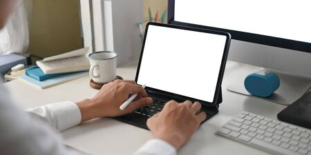 A smart man is using a white blank screen computer tablet at the white working desk.