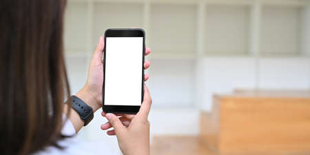 Behind of woman is holding a white blank screen smartphone while standing over blurred background.