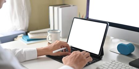 Cropped image of a businessman is using a white blank screen computer tablet at the white working desk. Фото со стока