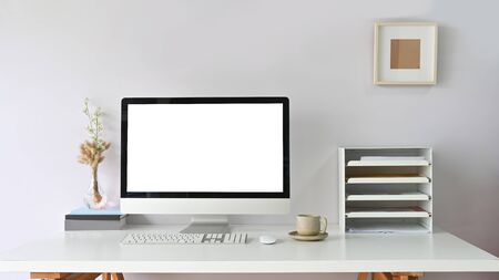 Workspace Computer monitor with white blank screen putting on working desk and surrounded by bookshelf, mouse, keyboard, coffee cup.