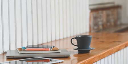 Close up image of the coffee cup is putting on a wooden plank that surrounded by laptop, tablet, smartphone, and equipment.