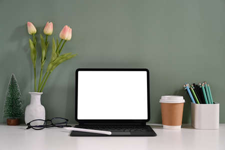 Computer tablet with a white blank screen is putting on a working desk surrounded by various equipment.