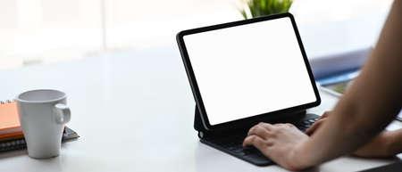 Woman typing on a blank screen tablet on wooden office desk. 免版税图像