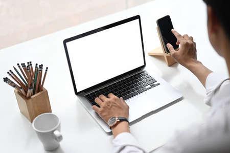 man typing on a blank screen laptop on wooden office desk.