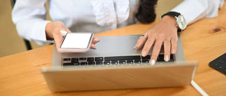 Close up woman typing laptop computer with empty screen. 免版税图像
